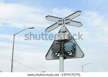 A mechanism on the back of a Saint Andrews Cross or cross buck a sign for level crossing intersection where a railway line crosses a road or path #1499570741