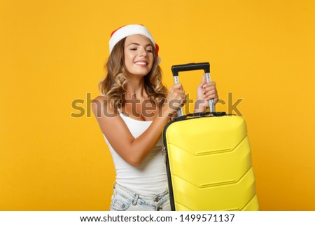 Joyful young Santa girl in white shirt, Christmas hat posing isolated on yellow wall background, studio portrait. Happy New Year 2020 celebration holiday concept. Mock up copy space. Holding suitcase #1499571137