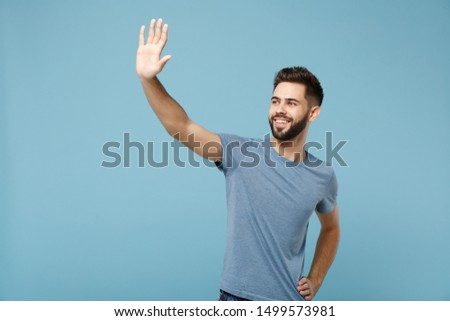 Young smiling man in casual clothes posing isolated on blue wall background in studio. People sincere emotions lifestyle concept. Mock up copy space. Waving and greeting with hand as notices someone #1499573981