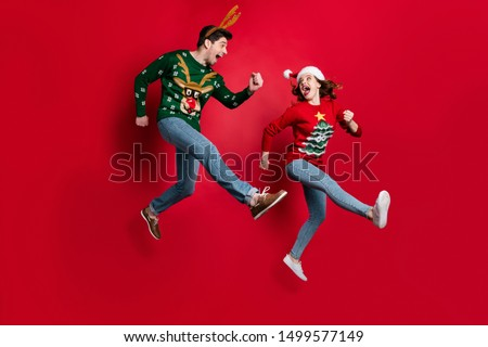 Full size photo of excited jumping couple run fast for x-mas discounts shopping wear ugly ornament jumpers isolated red color background #1499577149