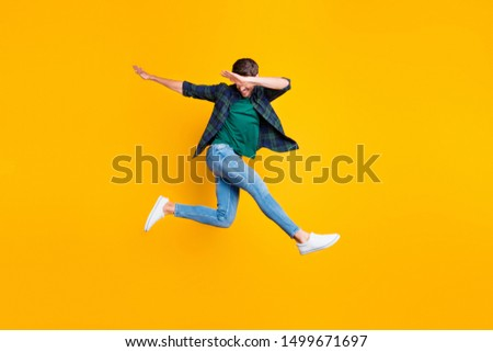 Full body photo of cheerful content dream funky man jump have fun dance like true clubber  enjoy summer vacation wear denim jeans sneakers checked green shirt isolated over yellow color background #1499671697