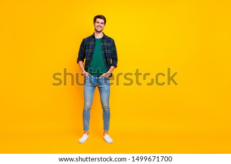 Full length body size photo of handsome man holding hands in jeans pockets wearing plaid shirt denim footwear stand isolated over bright color background standing posing confidently #1499671700