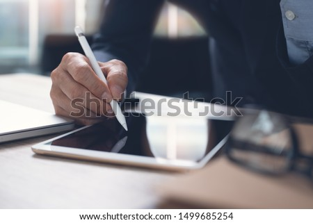 Businessman hand working with stylus pen on digital tablet with laptop computer in modern office, close up. Business man signing contract on tablet pc via mobile apps. electronic signature concept Royalty-Free Stock Photo #1499685254