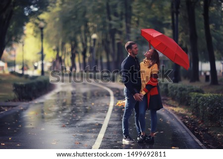 two people under an umbrella / a man and a woman are walking in a park with an umbrella, walking in the fall in the rain, an autumn umbrella #1499692811