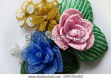 Beaded flowers on a white background. Blue bead flower, pink bead flower, yellow bead flower. Flowers from beads. Three flower from beads on a white background. #1499701403