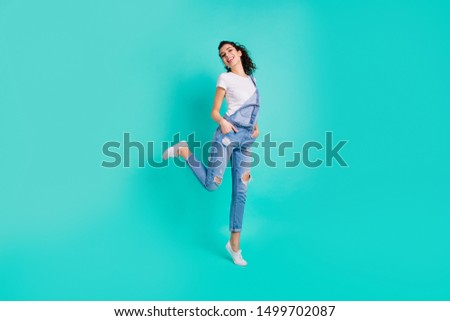 Full length body size view of her she nice attractive lovely cheerful cheery girl wearing blue overall standing on one leg tiptoe free time isolated on bright vivid shine green turquoise background #1499702087