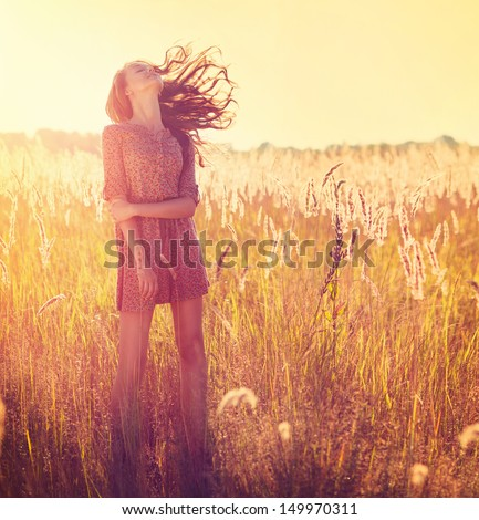 Beauty Romantic Girl Outdoors. Beautiful Teenage Model girl Dressed in Casual Short Dress on the Field in Sun Light. Blowing Long Hair. Autumn. Glow Sun, Sunshine. Backlit. Toned in warm colors