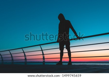 Silhouette of man in a hood with nice colored background #1499745659