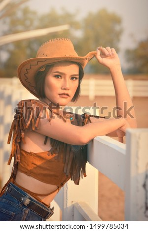 young woman cowgirl leaning on white fence in village. Beautiful Asian girl. Happy woman day