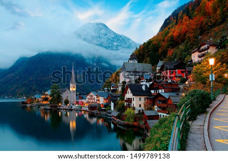 Fall scenery of Hallstatt at dawn, a peaceful lakeside village & a UNESCO heritage site in Salzkammergut region of Austria, with beautiful reflections in lake water & majestic mountains in background #1499789138