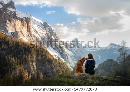 girl with a toller dog in the mountains. Autumn mood. Traveling with a pet. Nova Scotia Duck Tolling Retriever Royalty-Free Stock Photo #1499792870