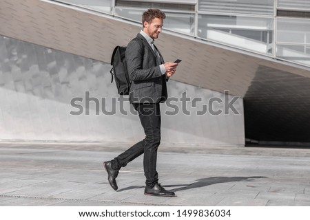 Happy young business man using phone walking on commute commuting to work with backpack bag on city street. Businessman texting looking at smartphone. #1499836034