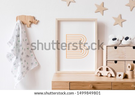 Stylish scandi childroom withwooden mock up photo frame, wooden toys, boxes, blocks and accessories Stars pattern on the background wall. Bright and sunny interior with wooden desk. Home decor. Royalty-Free Stock Photo #1499849801