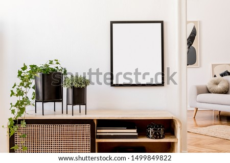 Modern scandinavian home interior with mock up photo frame, design wooden commode, plants in black pots, gray sofa, books and personal accessories. Stylish home decor. Template. Ready to use.  #1499849822
