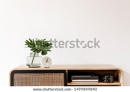 Interior design of living room at scandinavian apartment with stylish commode, tropical leaf in vase, books, white clock and elegant accessories. Modern home decor. Template. Copy space. White walls. #1499849840