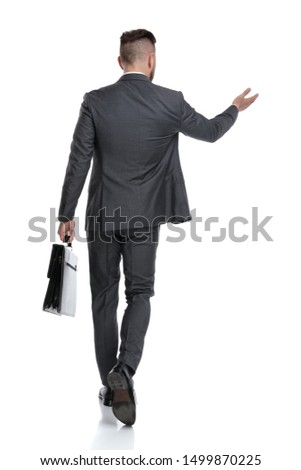 rear view of a confident businessman holding briefcase and welcomes or points hand to something, isolated on white background #1499870225