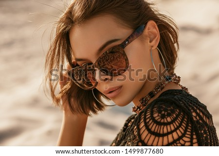 Outdoor close up portrait of young beautiful woman with tanned skin wearing luxury wide frame square sunglasses, hoop earrings, crochet top, posing on sand, at sunset. Copy, empty space for text  Royalty-Free Stock Photo #1499877680