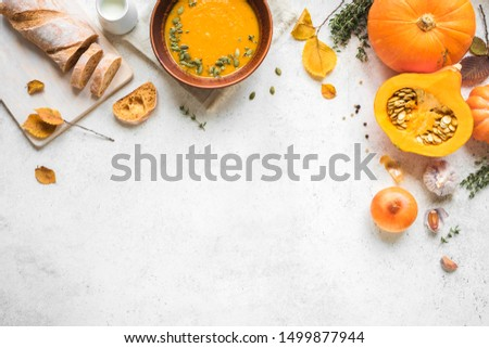 Pumpkin soup and organic pumpkins on white background, copy space. Seasonal autumn food - Spicy pumpkin soup with thyme and pumpkin seeds. #1499877944