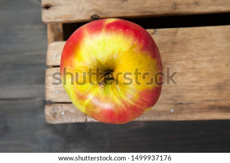 View from above. A ripe yellow-red apple lies on the corner of a wooden crate.
