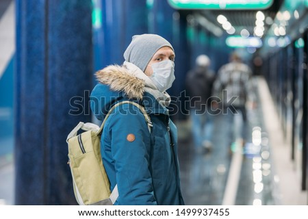 Ill young man feeling sick, wearing protective mask against transmissible infectious diseases and as protection against the flu in public and transportation. #1499937455