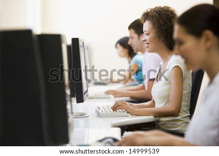 Four people in computer room typing and smiling #14999539
