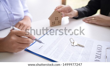 estate agent giving house keys present price for loan investment to home ownership for buy house contract.  #1499977247