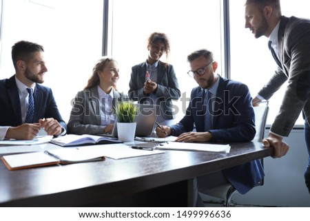Group of modern business people in formalwear discussing business and smiling while sitting in the office #1499996636