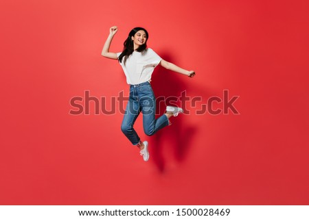 Mischievous girl in white T-shirt and jeans jumping on red background Royalty-Free Stock Photo #1500028469