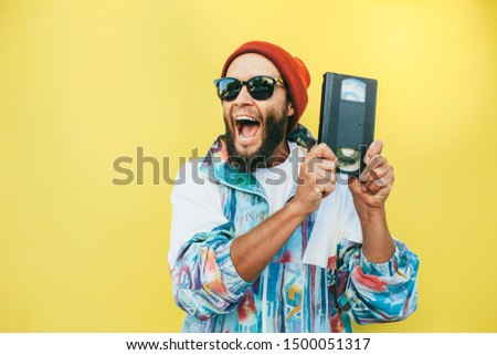Stylish young hipster man with beard in red hat, sunglasses and a retro jacket of 90s with VHS cassette on yellow background. #1500051317