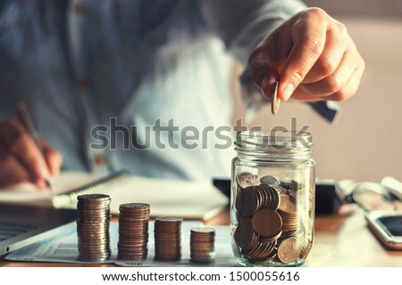 saving money with hand putting coins in jug glass concept financial #1500055616