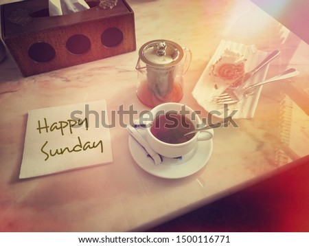 enjoy a cup of hot tea with a piece of cake on the table. Vintage color,  picture concept and a paper with the words 'Happy Sunday'.