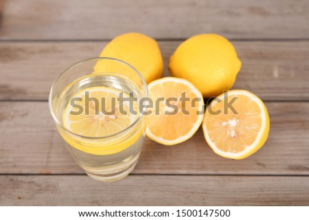 A cup of soaked lemon tea and freshly cut lemon fruit next to the cup #1500147500