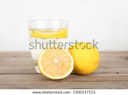 a glass of lemonade and a cup of lemon next to a full lemon and half cut #1500147515