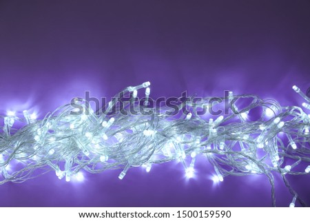 Glowing Christmas lights on dark violet background, top view. Space for text #1500159590