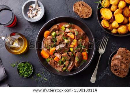 Beef meat and vegetables stew in black bowl with roasted baby potatoes. Dark background. Top view. #1500188114
