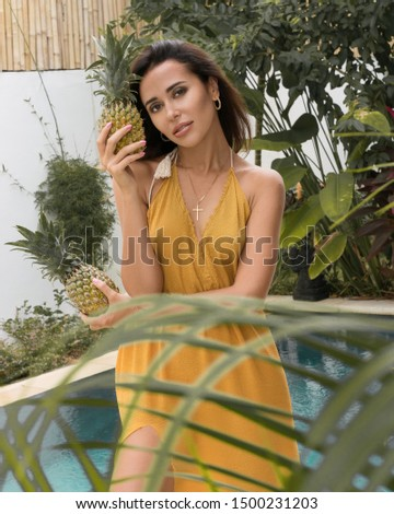 Woman in yellow dress with straw hat near the pool on tropical island Bali #1500231203