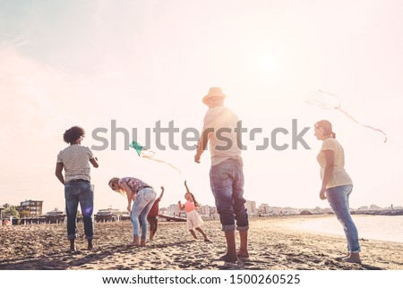 Happy familes flying with kite and having fun on the beach - Parents playing with children outdoor - Travel,love and holidays concept - Main focus on left couple #1500260525