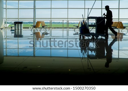 Silhouette of janitor cleaning service male guy on duty in artistic shot #1500270350