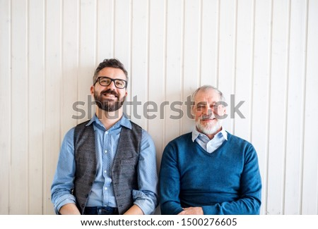 A portrait of adult hipster son and senior father sitting on floor indoors at home. #1500276605