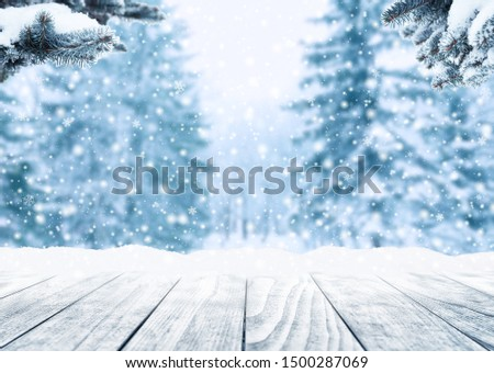 Wooden table top on winter sunny landscape with fir trees. Merry Christmas and happy New Year greeting background. Winter landscape with snow and christmas trees.