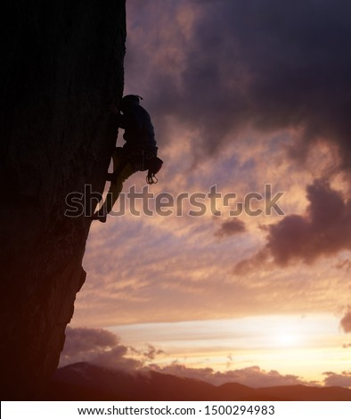 Male climber silhouette overcoming difficult path to top on challenging cliff in nightfall. Rock climbing. Cloudy sky with cumulonimbus over mountain peaks on background. Low angle view. Copy space #1500294983