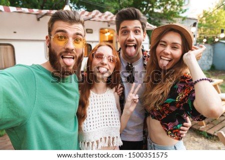 Group of cheerful excited friends standing at the trailer outdoors, taking a selfie #1500351575