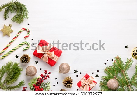 Christmas frame flat lay with pine, presents, golden elements, candy canes, confetti. Christmas template on dark wood #1500372977