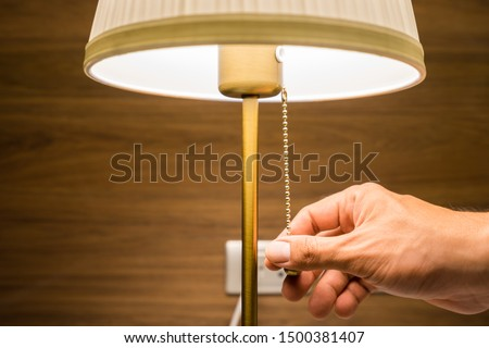 Hand of person is turning on or turning off the bedroom 's head lamp which is beautiful luxury-modern designed. Close up and selective focus photo. #1500381407