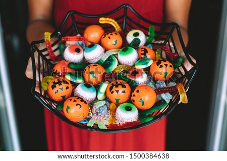 Woman at the front door offering funny Halloween candies on a spiderweb shaped bowl. Unrecognizable person #1500384638