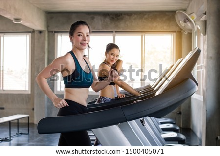 Happy Asian woman working out in gym together. Side view of two attractive sports women on running track.Sexy Girls on treadmill.Young woman workout working out running and cardio