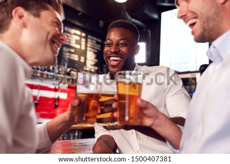 Three Men Making A Toast As They Meet For Drinks And Socialize In Bar After Work #1500407381