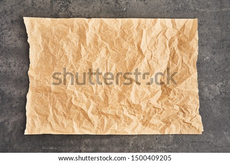Crumpled piece of brown parchment or baking paper on black concrete background. Top view. Copy space for text and design element. #1500409205