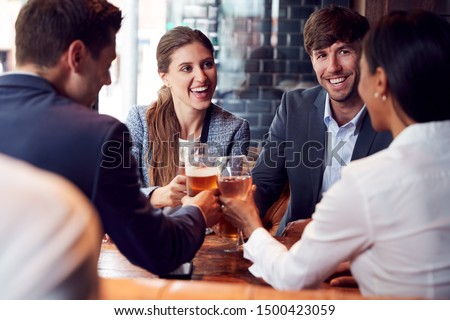 Group Of Business Colleagues Making A Toast As They Meet For Drinks And Socialize In Bar After Work #1500423059