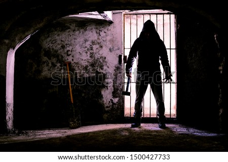 Scary dark man holding hammer inside dungeon - Silhouette of serial killer standing in creepy prison with threatening attitude - Concept of madness and murder - Backlight image with enhanced contrast #1500427733